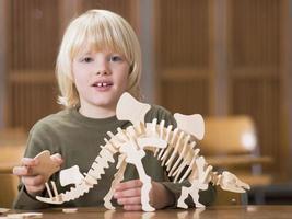 Junge sitzt mit Dinosaurierskelett foto