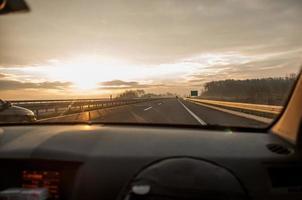 Blick aus einer Windschutzscheibe in einem Auto, das eine Autobahn entlang fährt foto