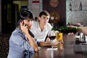Frau spricht auf ihrem Handy in der Kneipe foto