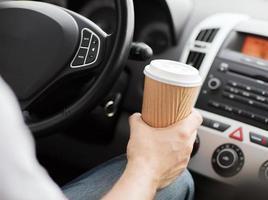 Mann, der während der Fahrt eine Tasse Kaffee zum Mitnehmen hat foto