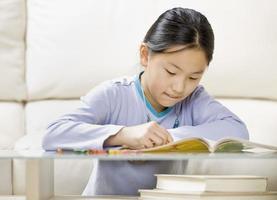 junges Mädchen Färbung in einem Malbuch foto