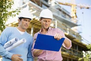 männliche Architekten mit Blaupause und Zwischenablage arbeiten vor Ort