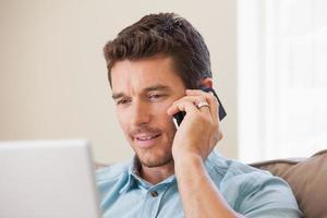 lächelnder Mann, der Laptop und Handy im Wohnzimmer benutzt foto