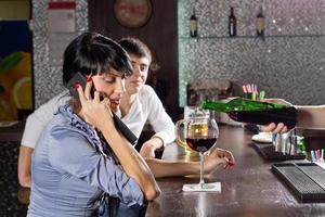 Frau plaudert auf ihrem Handy an der Bar foto