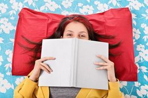 Mädchen im Bett versteckt ihr Gesicht hinter einem Buch foto
