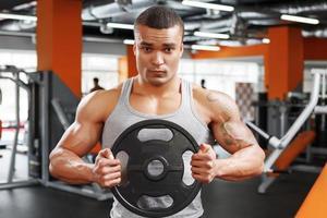 Powerlifter mit Gewichtsscheibe in den Händen foto