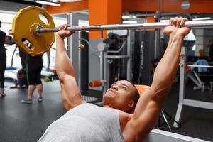 Liegender Mann, der Langhantel im Fitnessstudio hebt
