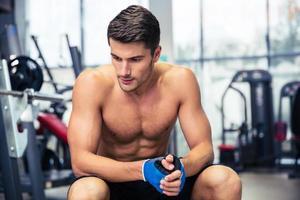 Mann, der auf der Bank im Fitnessstudio ruht foto