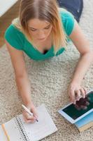 Frau, die auf dem Boden liegt und ihre Hausaufgaben mit Tablette macht