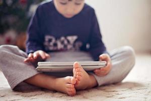 süße kleine Jungenfüße, Junge, der auf Tablette spielt foto