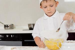 kleiner Koch, der die Konsistenz seines Teigs überprüft foto