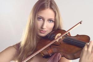 hübscher junger Geiger, der Geige spielt foto