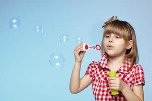 Mädchen bläst Seifenblasen foto