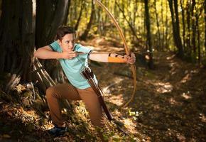 Mann Training in Holz mit Pfeil und Bogen. foto