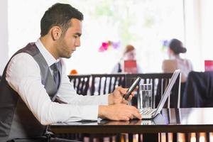 ernsthafter Geschäftsmann, der Telefon während der Arbeit am Laptop benutzt
