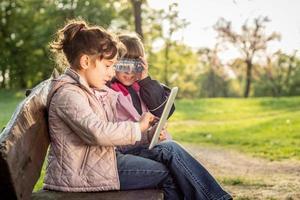 Foto von zwei kleinen Mädchen mit Tablette auf der Bank