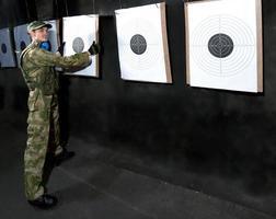 Mann mit Ziel im Schießstand foto