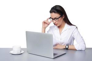 Geschäftsfrau, die online an einem Laptop arbeitet foto