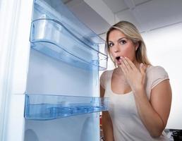 Frau, die im leeren Kühlschrank schaut foto