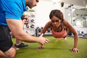 junge Frau macht Liegestütze unter Aufsicht eines Trainers
