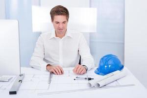 junger Architekt, der Plan auf Blaupause zeichnet foto