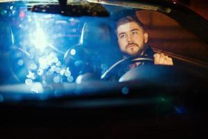 junger Mann, der seinen modernen Sportwagen fährt foto