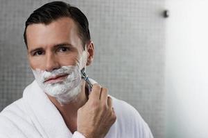 Mann rasiert sich im Badezimmer foto