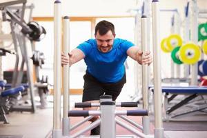 junger Mann, der mit Geräten in einem Fitnessstudio trainiert foto