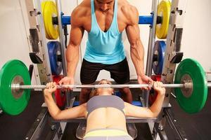 Frau Bankdrücken Gewichte mit Hilfe des Trainers, vorne v