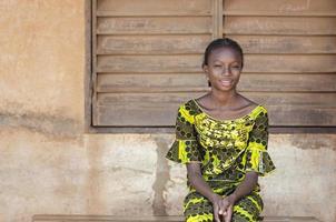 Symbol für den Schulanfang - hübsches schwarzafrikanisches Schulmädchen posiert foto