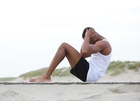 junger Mann, der am Strand trainiert und Sit-Ups macht foto