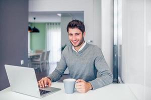junger lächelnder Geschäftsmann, der von zu Hause in einem grauen Thema arbeitet foto