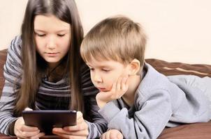 Kinder spielen auf dem Tablet horizontal foto