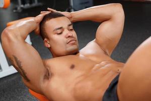 junger angenehmer Mann, der Bauchkrisen im Fitnessstudio tut