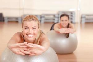 Frau, die sich auf Fitnessball streckt foto