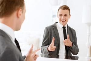 Mann schaut in den Spiegel und zeigt auf sich foto
