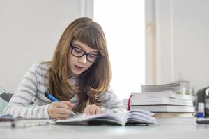 Teenager-Mädchen, das Hausaufgaben am Tisch im Haus macht