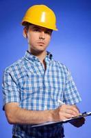Architekt im gelben Helm, der auf Zwischenablage schreibt