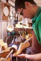 Der Schuhmacher-Schleifschuh hält in einer Werkstatt foto
