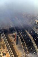 Gebäude und Autobahn sind mit dichter Nebelschicht bedeckt foto