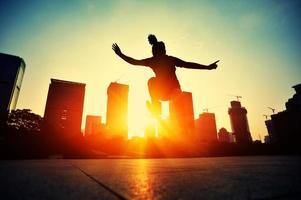 Skateboardfrau, die bei Sonnenaufgang springt foto