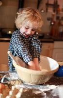 kleiner Junge, der Mehl mischt foto