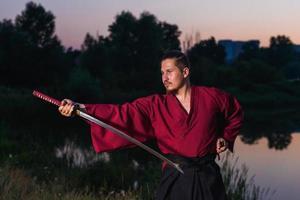 Mann in ethnischer Samurai japanischer Kleidungsuniform mit Katana-Schwert foto