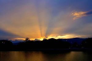 Wolkensonnenuntergang mit Sonnenstrahl und Schattenbildberg in der Zusammensetzung foto