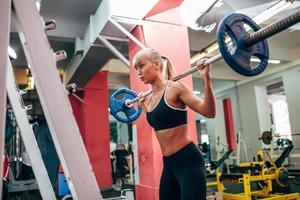 Fitness-Frau, die Langhantelkniebeugen in einem Fitnessstudio tut foto