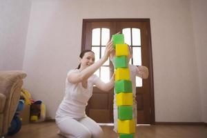 Mutter und Sohn bauen Turm aus bunten Würfeln foto