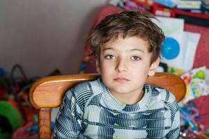 trauriger Junge, der Kamera betrachtet foto