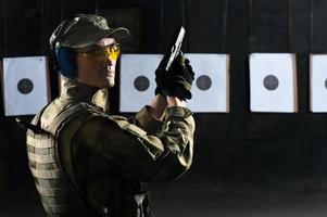 Mann schießt mit Waffe foto