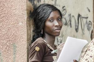 Lernsymbol: lächelndes junges afrikanisches Geschäftsmädchen, das Schreiben arbeitend studiert foto