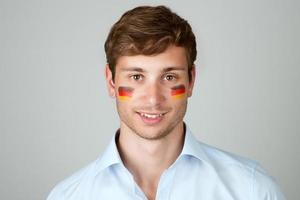 junger schöner Mann mit Flagge der deutschen Malerei im Gesicht foto
